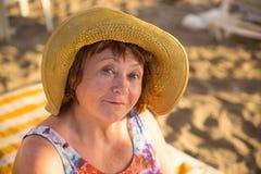 Sombrero que lleva sonriente de la mujer mayor en la playa en sunbed Imagen de archivo libre de regalías