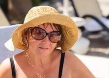 Sombrero que lleva sonriente y gafas de sol de la mujer mayor en la playa Imagen de archivo libre de regalías
