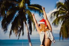 Sombrero rojo de la muchacha atractiva delgada joven de Santa Claus en smartphone de la Navidad Foto de archivo