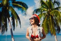 Sombrero rojo de la muchacha atractiva delgada joven de Santa Claus en smartphone de la Navidad Fotografía de archivo