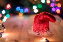 Sombrero rojo de la Navidad en la tabla en las guirnaldas de un fondo Imágenes de archivo libres de regalías