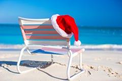 Sombrero rojo de Papá Noel del primer en longue de la silla en tropical Foto de archivo libre de regalías