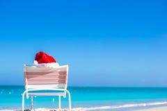 Sombrero rojo de Papá Noel del primer en longue de la silla en tropical Fotografía de archivo libre de regalías