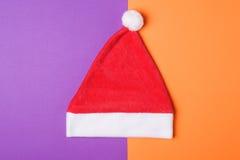 Sombrero rojo de Santa Claus en la naranja y el fondo de papel del wiolet, estilo mínimo Foto de archivo