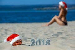 Sombrero rojo de Santa Claus que lleva en la bola de la Navidad que miente en la playa, al lado de la arena del Año Nuevo con las Foto de archivo