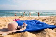 Sombrero, toalla, gafas de sol y deslizadores en una playa tropical Fotografía de archivo