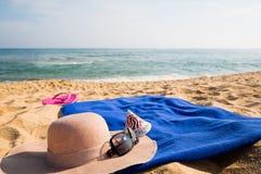 Sombrero, toalla, gafas de sol y deslizadores en una playa tropical Fotos de archivo libres de regalías
