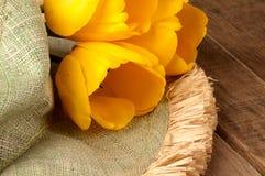 Sombrero verde con el tulipán amarillo tres en la madera rústica Fotografía de archivo libre de regalías