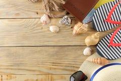 Sombrero, vidrios, chancletas y cáscaras del concepto del viaje en una tabla de madera natural Relajación holidays Visión superio foto de archivo