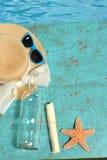 Sombrero, vidrios, mensaje, botella y estrellas de mar Imagen de archivo