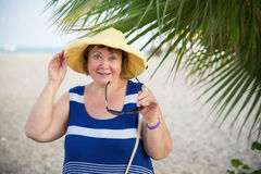Sombrero womanwearing mayor sonriente debajo de las palmeras Imágenes de archivo libres de regalías