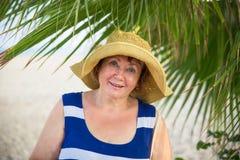Sombrero womanwearing mayor sonriente debajo de las palmeras Fotos de archivo