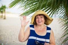 Sombrero womanwearing mayor sonriente debajo de las palmeras Fotografía de archivo libre de regalías