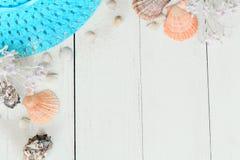Sombrero y conchas marinas de paja del verano en un fondo de madera Foto con el lugar para el texto Fotografía de archivo libre de regalías
