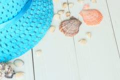 Sombrero y conchas marinas de paja en fondo de madera Foto con el lugar para el texto Fotografía de archivo