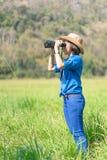 Sombrero y control del desgaste de mujer binoculares en campo de hierba Fotografía de archivo