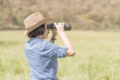 Sombrero y control del desgaste de mujer binoculares en campo de hierba Foto de archivo libre de regalías