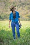 Sombrero y control del desgaste de mujer binoculares en campo de hierba Fotos de archivo