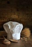 Sombrero y cucharas del cocinero con el fondo del ladrillo Imágenes de archivo libres de regalías