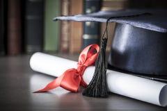 Sombrero y diploma de la graduación en la tabla fotografía de archivo