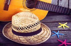 Sombrero y estrellas de mar de la estrella de la guitarra acústica en un fondo de madera del grunge Foto de archivo