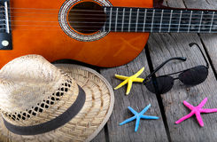 Sombrero y estrellas de mar de la estrella de la guitarra acústica de la barra de la playa del fondo del verano en una madera Fotografía de archivo libre de regalías