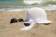 Sombrero y gafas de sol blancos de mimbre en la playa Fotografía de archivo libre de regalías