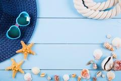Sombrero y gafas de sol con las cáscaras, las estrellas de mar y la cuerda en la madera azul Imagen de archivo libre de regalías
