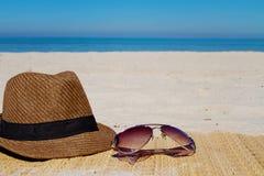 Sombrero y gafas de sol de la moda del verano en una playa Foto de archivo