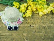 Sombrero y gafas de sol del ` s de los niños con las flores en una tabla de madera Foto de archivo