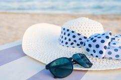Sombrero y gafas de sol en la playa Fotos de archivo libres de regalías
