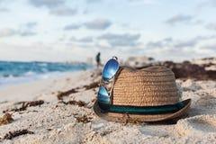 Sombrero y gafas de sol en Sandy Shore In The Summer foto de archivo libre de regalías