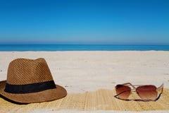Sombrero y gafas de sol en una playa en verano Imagen de archivo libre de regalías