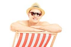 Sombrero y gafas de sol que llevan sonrientes del individuo, presentando en una silla de playa Imagen de archivo libre de regalías