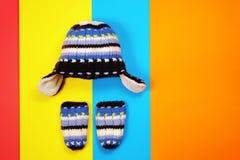 Sombrero y manoplas hechos punto en fondo multicolor fotografía de archivo