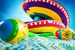 Sombrero y maracas en un fondo coloreado Foto de archivo libre de regalías