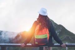 Sombrero y mochila que llevan de la mujer que viajan que se sientan arriba en el top de la montaña con el pelo que agita, igualan Imagen de archivo libre de regalías
