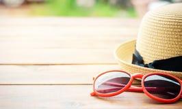 Sombrero y moda roja de las gafas de sol en la madera Fotos de archivo libres de regalías