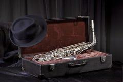 Sombrero y saxofón en una maleta vieja Fotografía de archivo