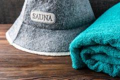 Sombrero y toalla de la sauna en fondo de madera oscuro Accesorios del baño foto de archivo libre de regalías