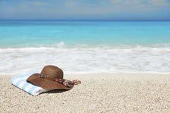 Sombrero y toalla en una playa Fotografía de archivo libre de regalías