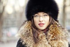 Sombrero y vidrios de piel de la mujer que llevan Foto de archivo