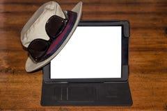 Sombrero y vidrios en una tableta digital Fotografía de archivo