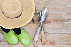 Sombrero, zapatos que cultivan un huerto y herramientas en el fondo de madera Fotos de archivo libres de regalías