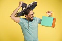 Sombrerohut des Mannfr?hlichen gesichts h?lt gelben Hintergrund der Einkaufstasche Kerl mit dem Bart festlich im Sombrero Mann fe stockfotografie