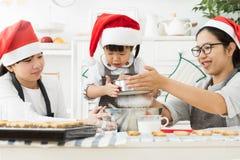 Sombreros asiáticos felices de Papá Noel del desgaste de la familia que asperjan la pasta con flo Imagen de archivo