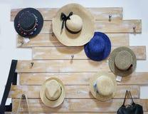 Sombreros bonitos hechos a mano de las mujeres Sombreros clásicos del verano que cuelgan en una tienda en un fondo de la pared Ac Foto de archivo