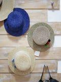 Sombreros bonitos hechos a mano de las mujeres Sombreros clásicos del verano que cuelgan en una tienda en un fondo de la pared Ac Fotos de archivo