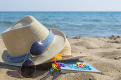 Sombreros de paja, gafas de sol y un libro en la playa Vacaciones de verano Fotos de archivo libres de regalías