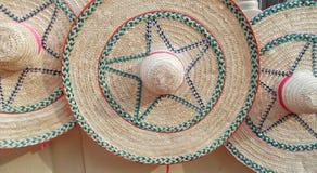 Sombreros de paja grandes de las mujeres elegantes y coloridos en el paseo de la calle de mercado durante verano el días soleados foto de archivo libre de regalías